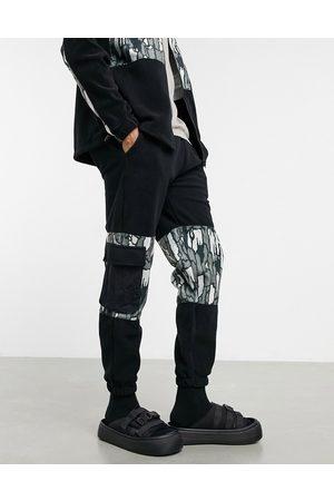 adidas – Schmal zulaufende Jogginghose in aus Polarfleece mit Einsätzen mit abstraktem Military-Muster und Utility-Taschen, Kombiteil